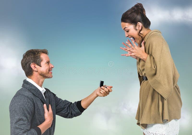 Man het propsing aan vrouw tegen blauwgroene achtergrond met wolken royalty-vrije stock afbeelding