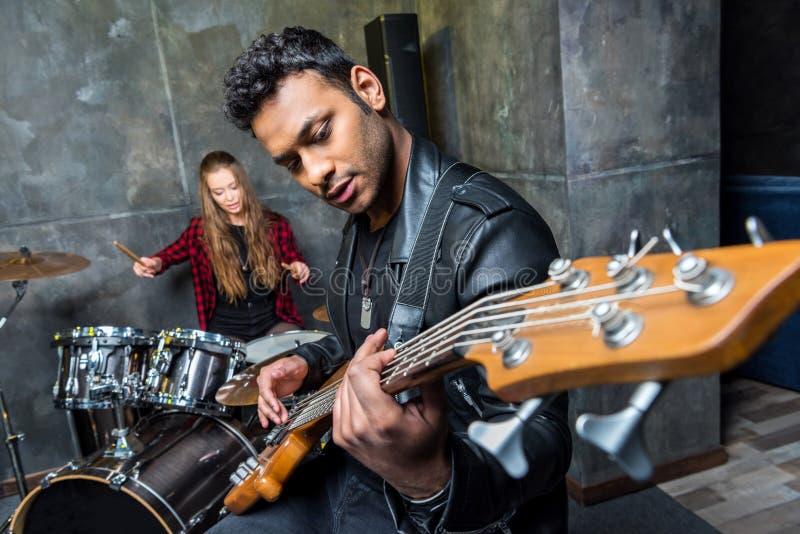 Man het spelen de gitaar met vrouw het spelen trommels, rots - en - rolt bandconcept stock afbeelding