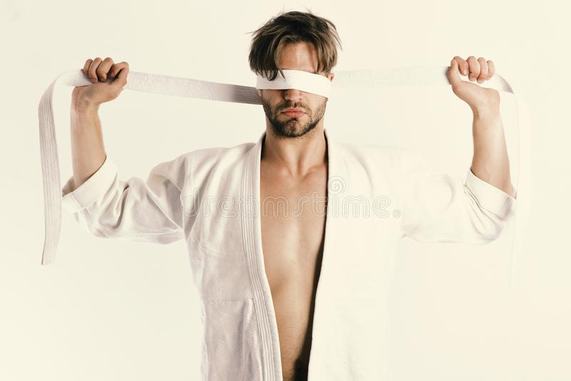 Man with hidden face and bristle isolated on white background. Karate fighter with strong body holds white belt. Guy posing in white kimono ties eyes with belt royalty free stock image