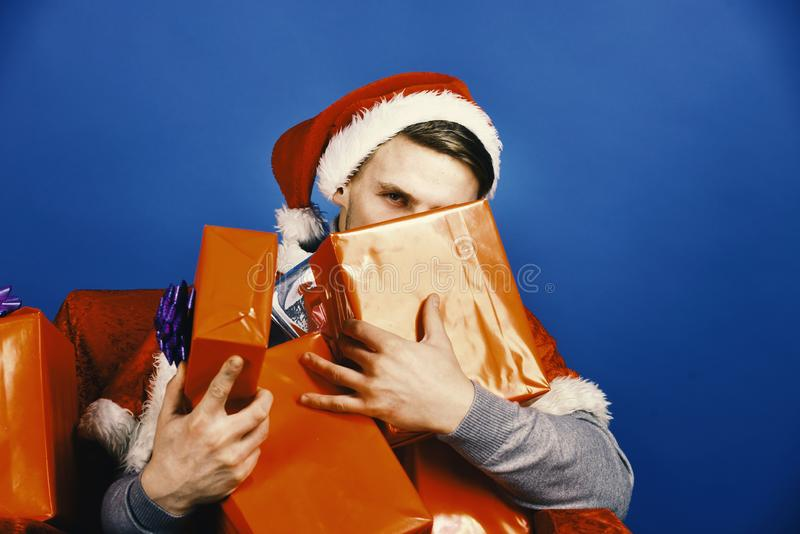 Man hides behind xmas gifts. Santa with many presents. On blue background. Guy looks out of red and silver boxes. Surprise and presents concept royalty free stock photos