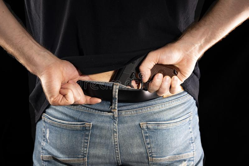 Man hides a gun behind a trouser belt on a black background.  royalty free stock photography