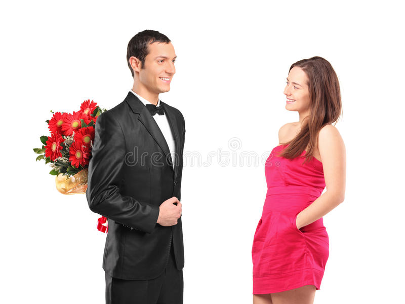 Man hiding bouquet of flowers from a woman