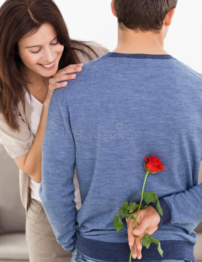 Man Hiding A Flower Behind His Back For His Wife Stock Photo
