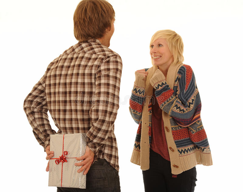 Man hiding gift. Man holding gift for a woman behind his back stock photos