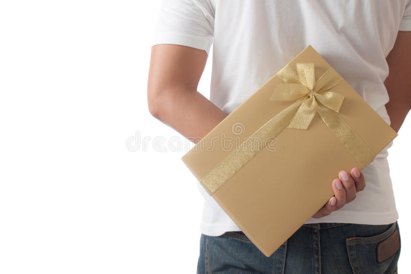 Man hiding a golden gift box giving stock images