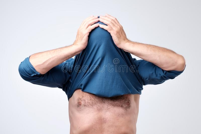 Man hiding his face with undershirt. Human hid head with t-shirt. Anonymous concept stock image