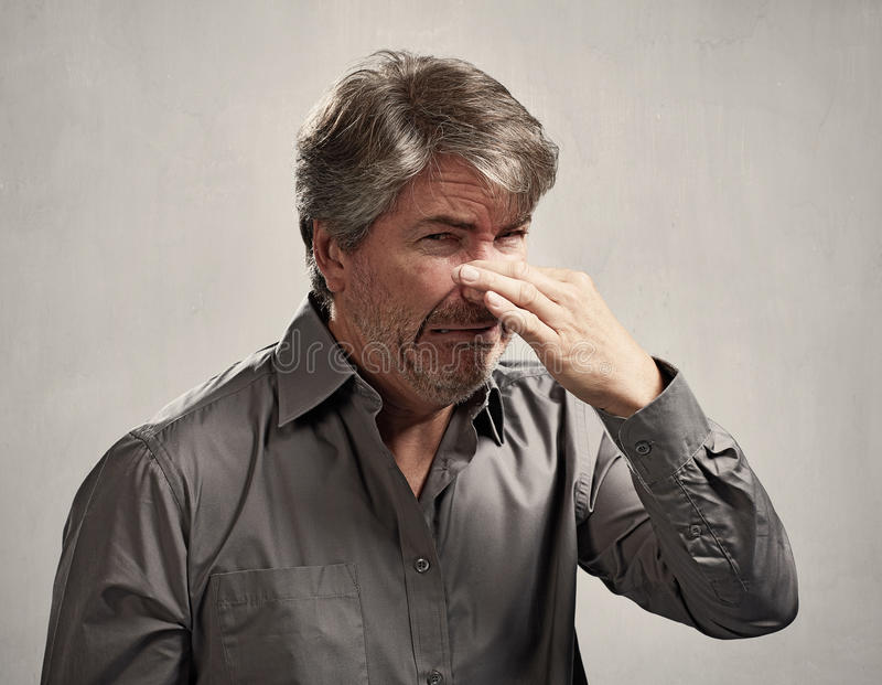 Man hiding his nose. Bad smell over gray background stock photo