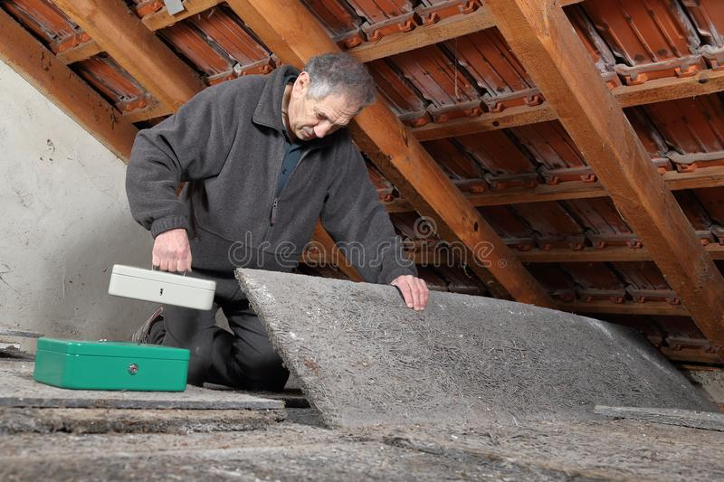 Man hiding valuables money at a hiding place in house stock photos