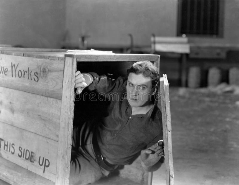 Man hiding in wooden crate. (All persons depicted are no longer living and no estate exists. Supplier grants that there will be no model release issues stock image