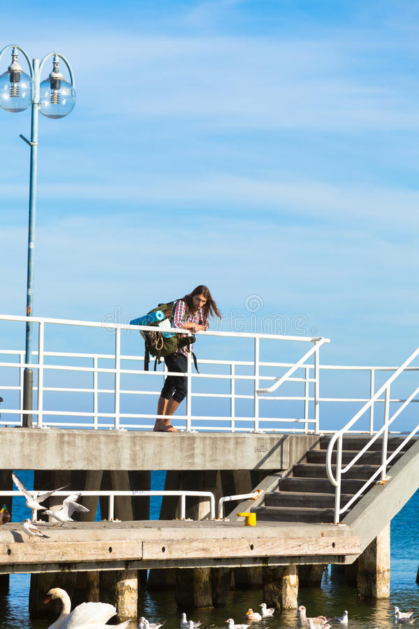 Man hiker with backpack on pier, sea landscape stock photo