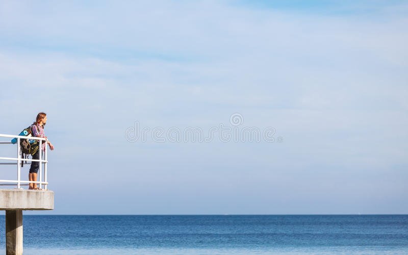 Man hiker with backpack on pier, sea landscape royalty free stock image