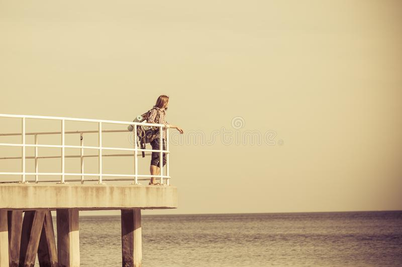 Man hiker with backpack on pier, sea landscape royalty free stock photography