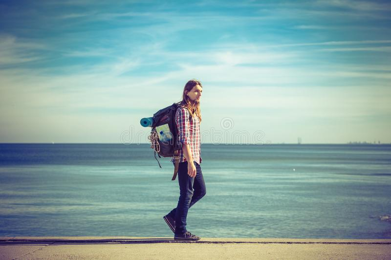 Man hiker with backpack tramping by seaside. Man hiker backpacker walking with backpack by seaside at sunny day. Adventure, summer, tourism active lifestyle stock image