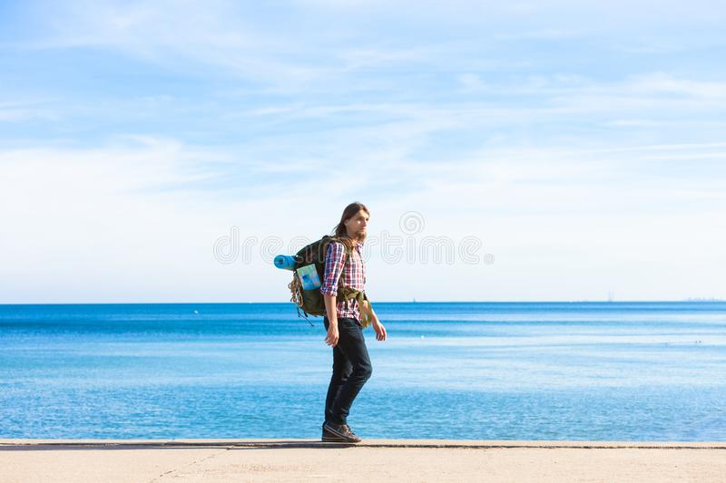 Man hiker with backpack tramping by seaside stock image
