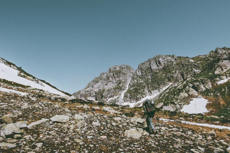 Man hiker with backpack trekking in rocky mountains stock images