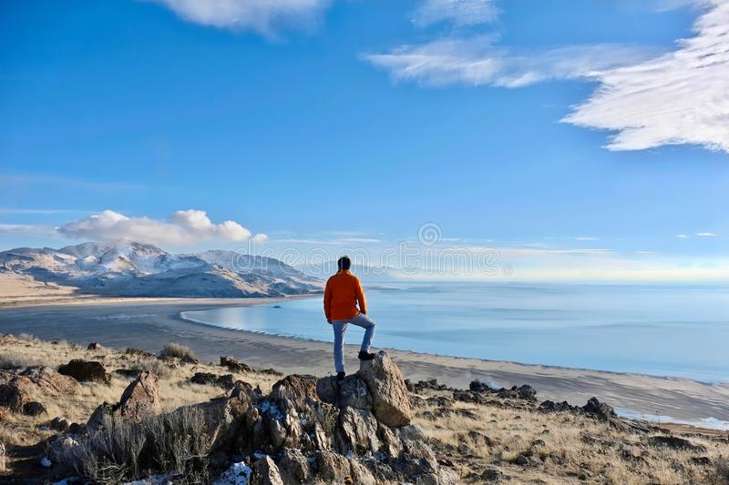 Travelling to Great Salt Lake and Antelope Island in a winter day. Man hiker on a cliff above the lake enjoying the scenic views. Salt Lake City. Antelope royalty free stock images