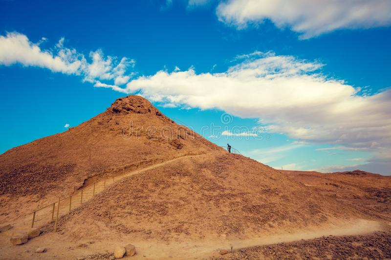 A man hiker climbs up a mountain stairs. Ascent to Masada from the west stock photo