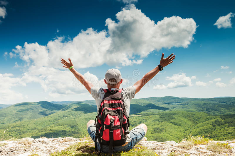 Man hiker greeting rich nature on the top of mountain stock photo