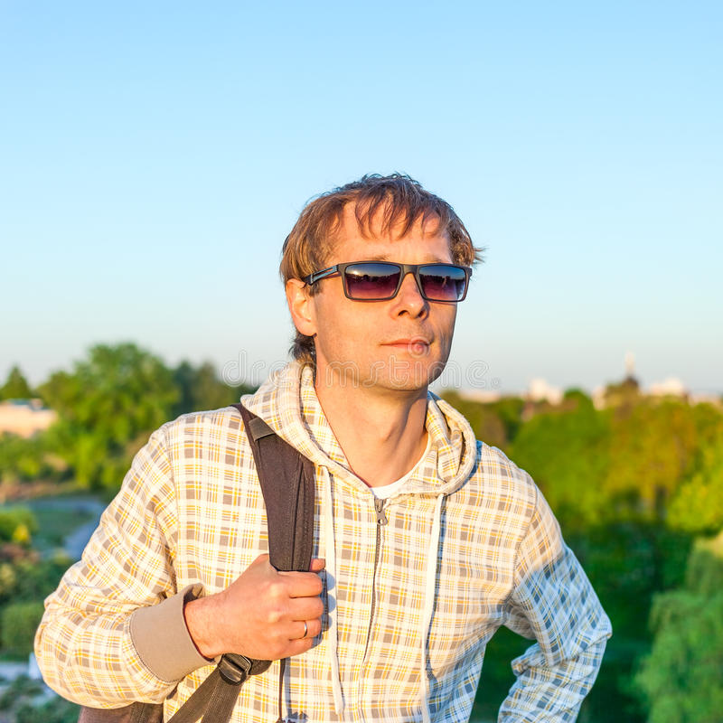 Man hiker holding backpack and looking at the sunset stock photography