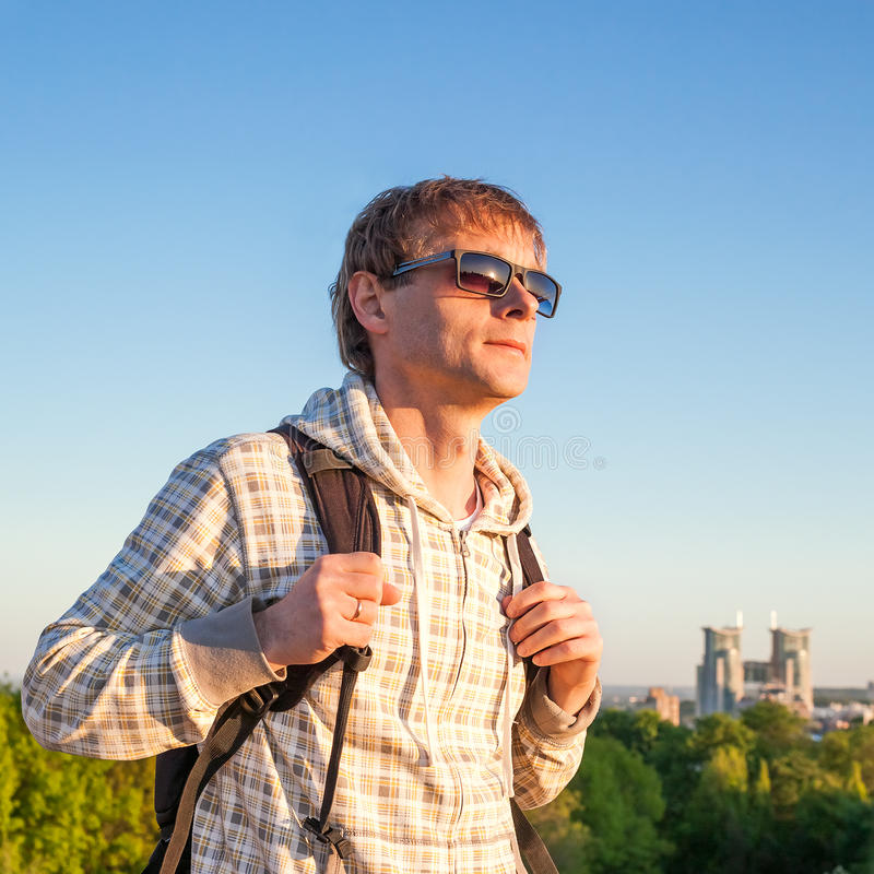 Man hiker holding backpack and looking at the sunset stock photos