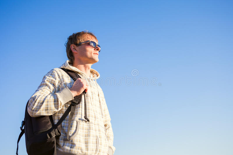 Man hiker holding backpack and looking at the sunset royalty free stock photography