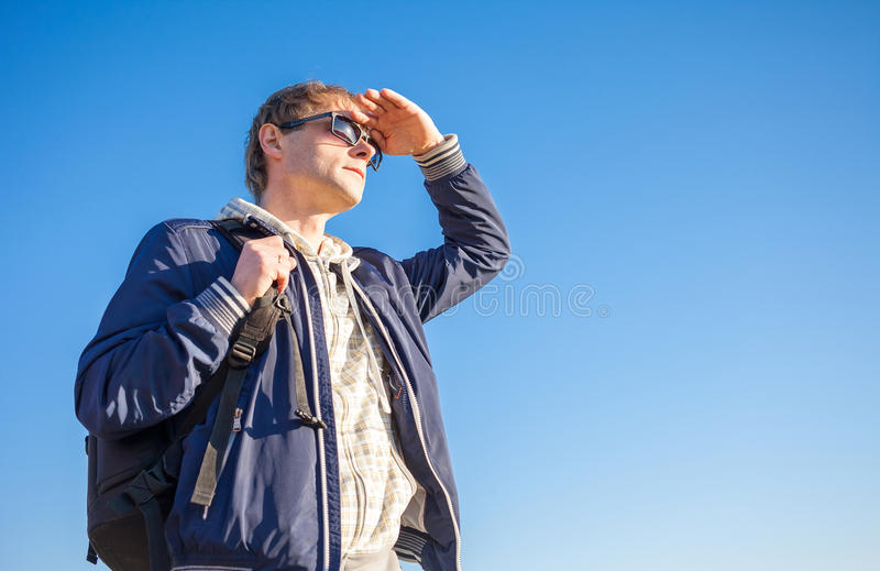 Man hiker holding backpack on a sunny day against a blue sky royalty free stock images