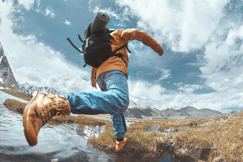 Man hiker jumps across water in mountain area stock image
