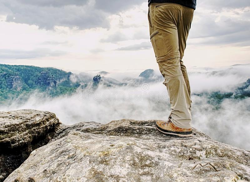Man hiker legs with windproof trousers and hiking boots. On mountain peak rock with a valley at background stock images