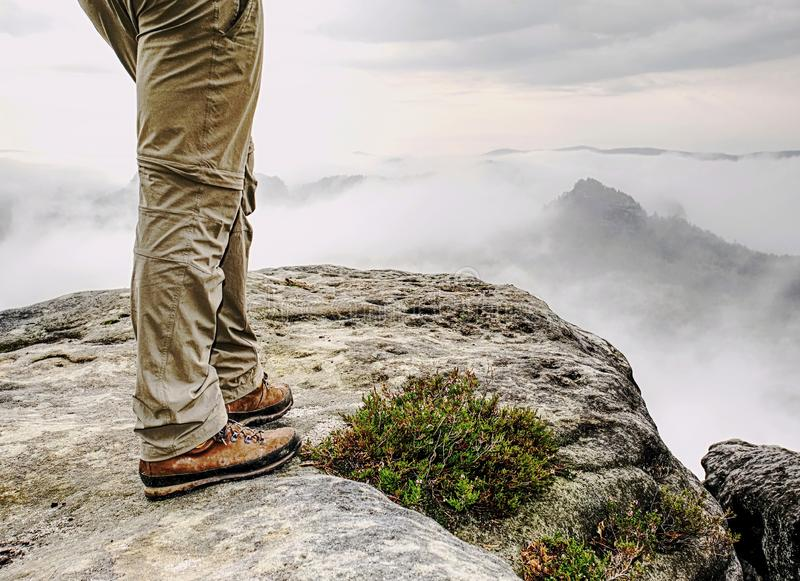Man hiker legs with windproof trousers and hiking boots. On mountain peak rock with a valley at background royalty free stock photo