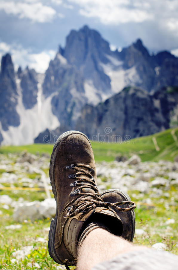 Man hiker lie on a ground. Peaks like a background. Sunny day.Trekking boots.Lens flare. Succesful backpacker enjoy a view. royalty free stock images