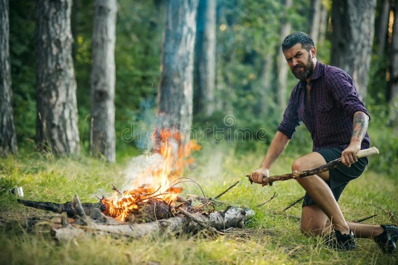 Man hiker make fire in forest stock photo