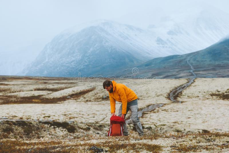 Man hiker packing backpack gear in mountains travel vacations adventure royalty free stock photo