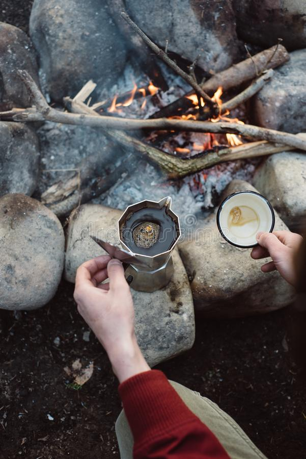 Man hiker pours itself hot coffee near to bonfire. Male sitting and holding a mug of coffee after hiking. Adventure concept royalty free stock images
