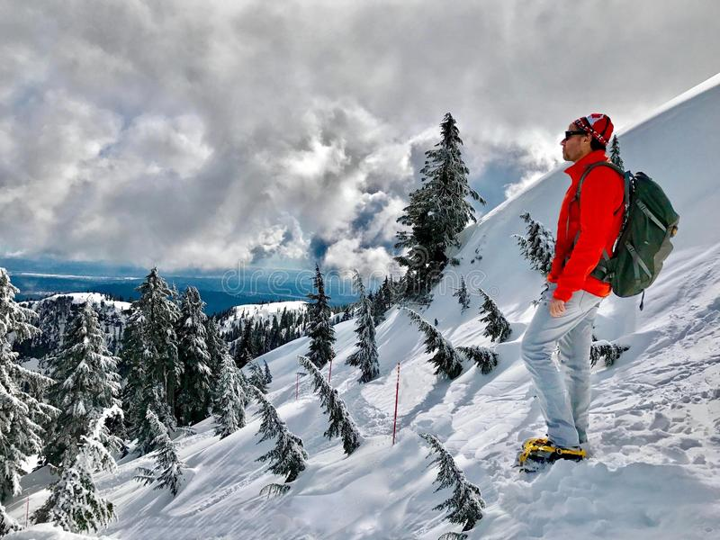 Man hiker in scenic winter mountains. Mount Seymour Park. Hiking trail to the first peak. North Shore. Vancouver. British Columbia stock images