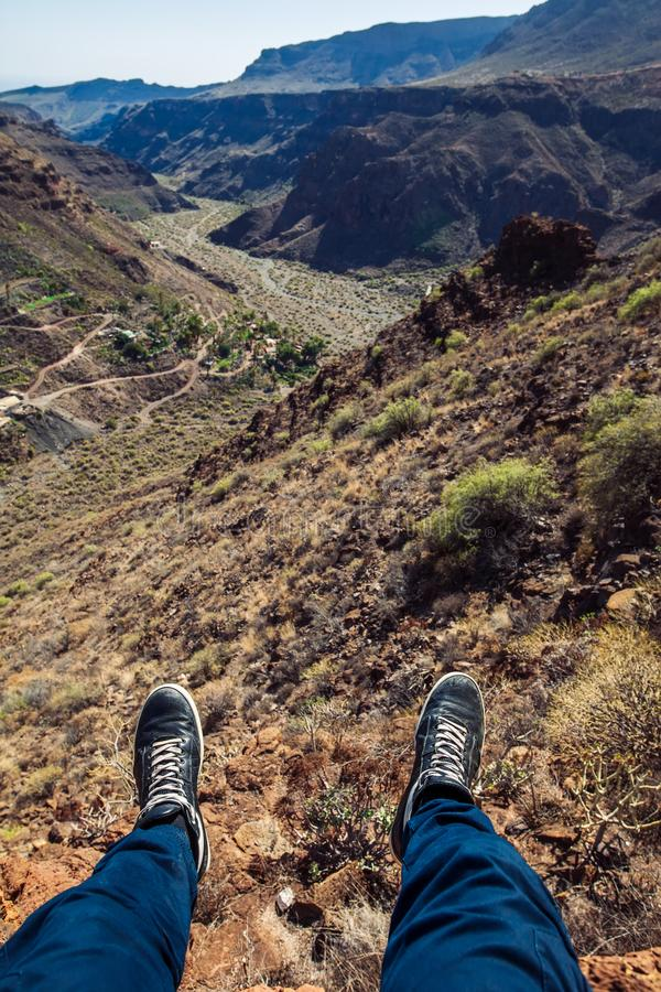 Man hiker sitting at the edge of a cliff. Legs over canyon stock images