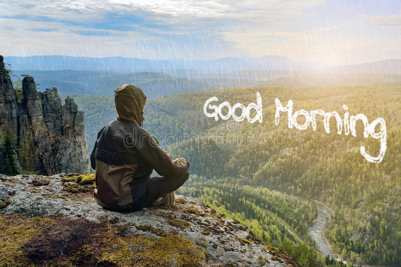 Man hiker sitting on top of mountain meeting sunrise, Good Morning lettering in form of clouds. Man hiker sitting on top of mountain meeting sunrise, Good royalty free stock images