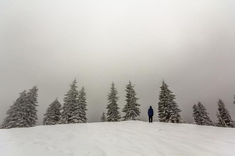 Man hiker standing in winter snow covered mountains enjoying vie stock photos