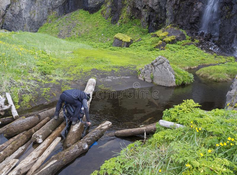 Man hiker standing on wooden log takeing up clean water, filling stock image