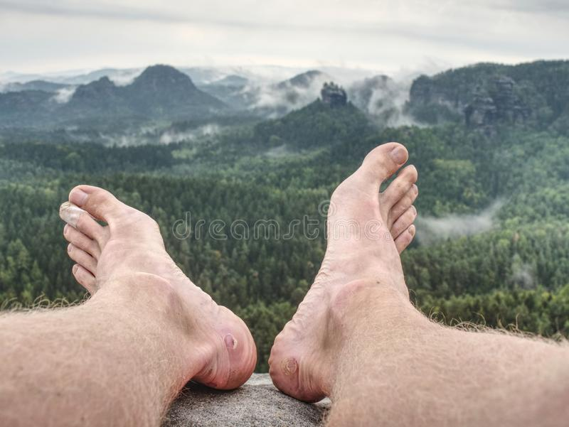 Man hiker take off sweaty boots on mountain rocks Beautiful weather royalty free stock photo