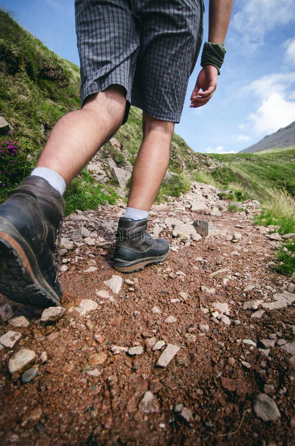 Man hiker walking on mountain rocks with sticks. Beautiful weather with Scotland nature. Detail of hiking boots on the difficult p royalty free stock photography