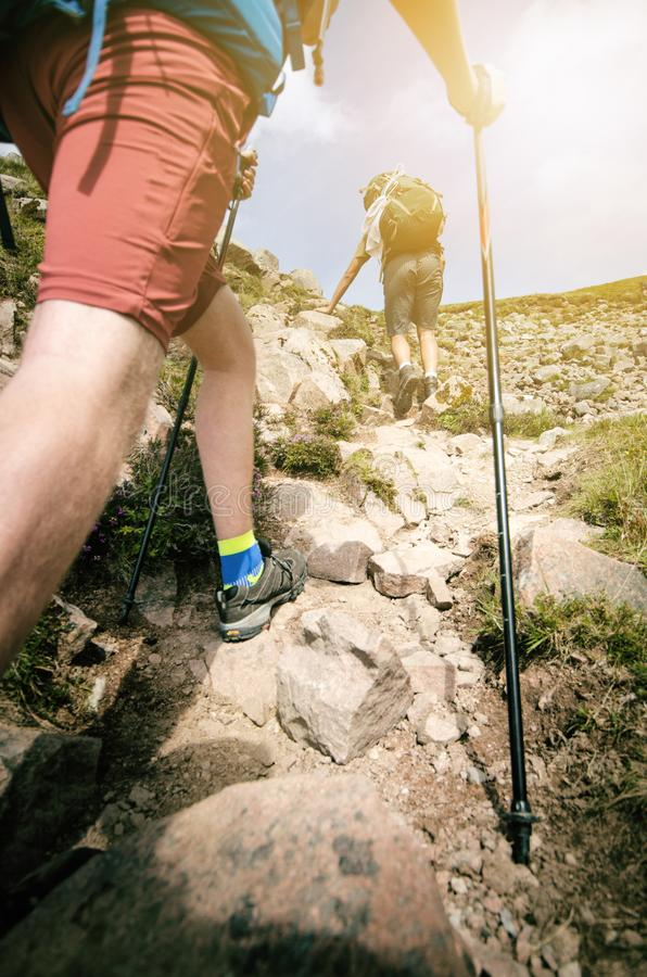 Man hiker walking on mountain rocks with sticks. Beautiful weather with Scotland nature. Detail of hiking boots on the difficult p stock images