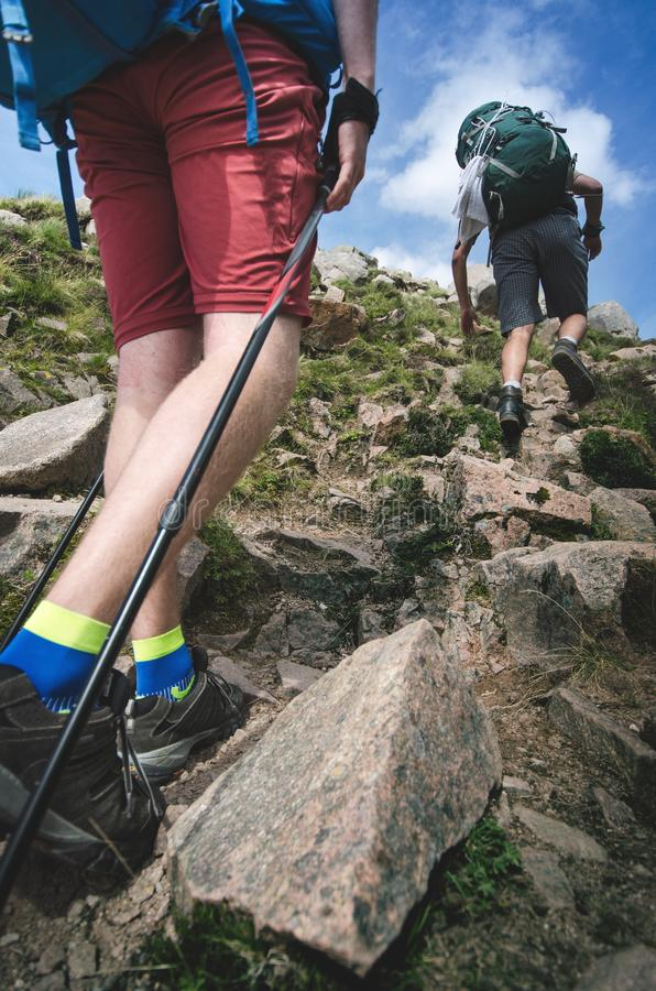 Man hiker walking on mountain rocks with sticks. Beautiful weather with Scotland nature. Detail of hiking boots on the difficult p. Athway, trail, Friends in the royalty free stock photo