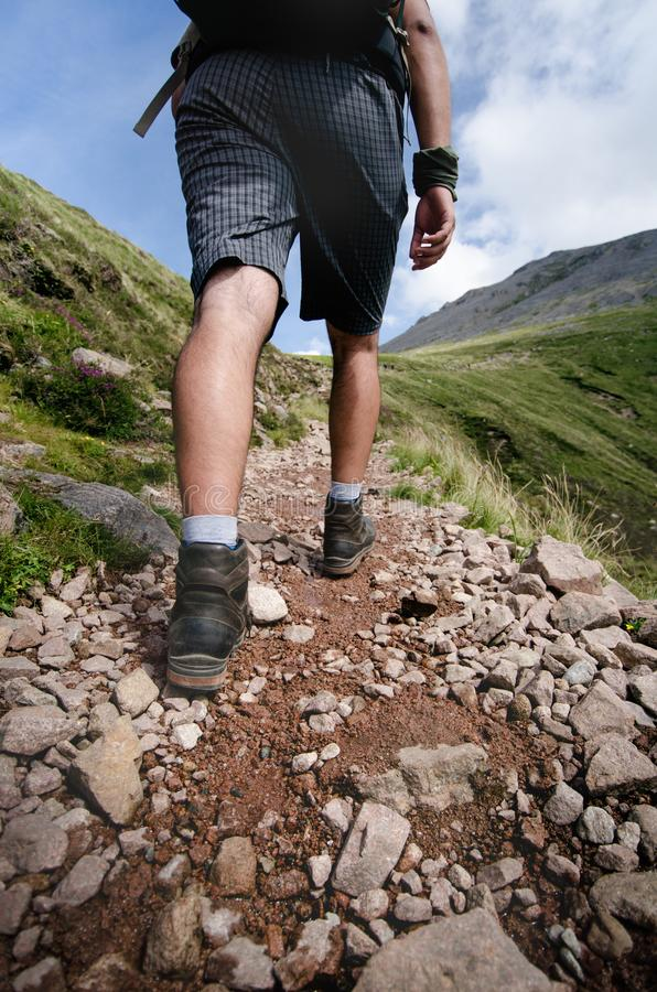 Man hiker walking on mountain rocks with sticks. Beautiful weather with Scotland nature. Detail of hiking boots on the difficult p stock photography