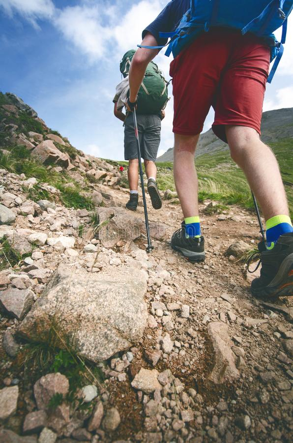 Man hiker walking on mountain rocks with sticks. Beautiful weather with Scotland nature. Detail of hiking boots on the difficult p stock image