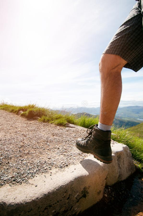 Man hiker walking on mountain rocks with sticks. Beautiful weather with Scotland nature. Detail of hiking boots on the difficult p stock photo