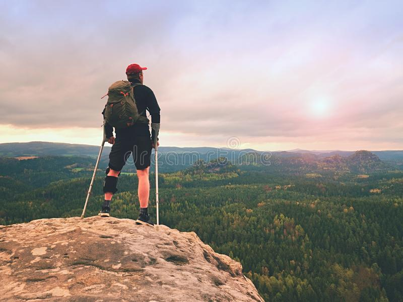 Man hiker Wearing Supportive Leg Brace and gainst the cruthes. Natural forest park royalty free stock image