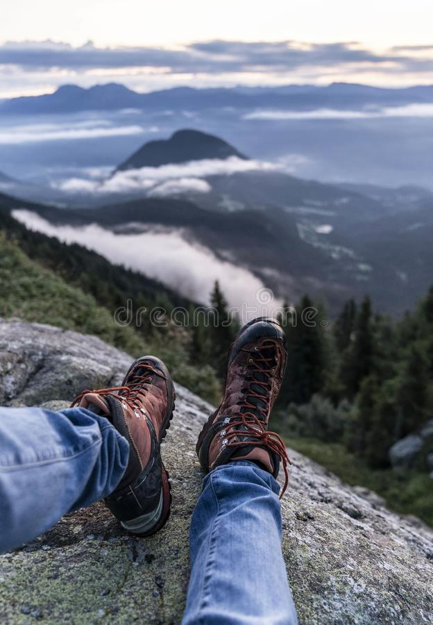Man hiking boots enjoying wonderful breathtaking mountain view. Freedom concept. Traveller sitting and making feet selfie on. Beautiful landscape with forest royalty free stock image