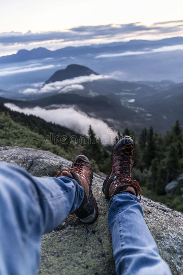 Man hiking boots enjoying wonderful breathtaking mountain view. Freedom concept. Traveller sitting and making feet selfie on. Beautiful landscape with forest stock photos