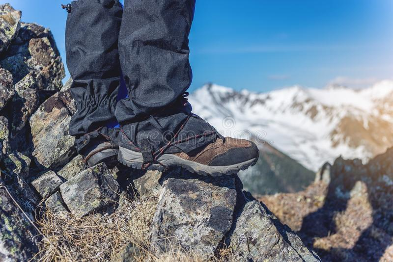 Man in Hiking boots stands on the rocks in front of the entrance to the peak on the background of the snowy mountains. A man in Hiking boots stands on the rocks royalty free stock image