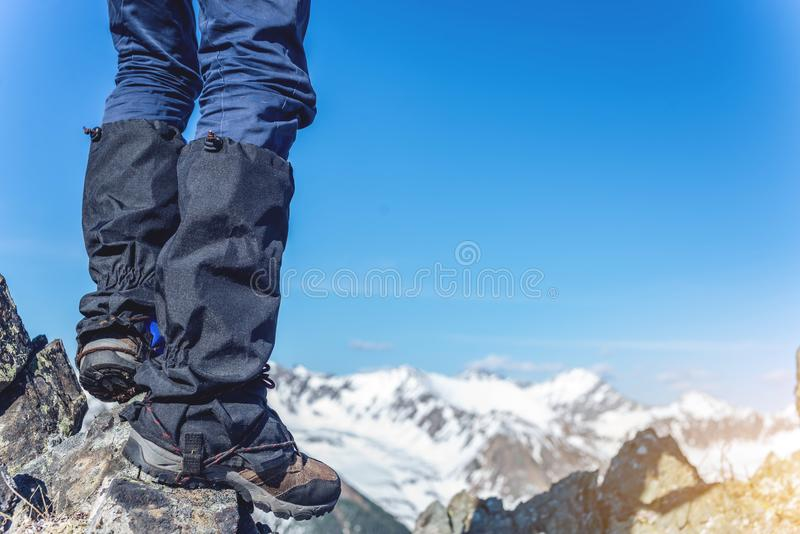 Man in Hiking boots stands on the rocks in front of the entrance to the peak on the background of the snowy mountains. A man in Hiking boots stands on the rocks royalty free stock images